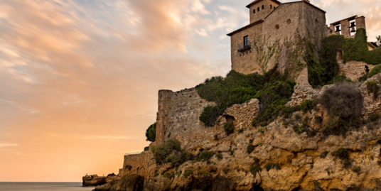 Castle of Tamarit on the rocks surrounded by the sea during the sunset in Altafulla in Spain